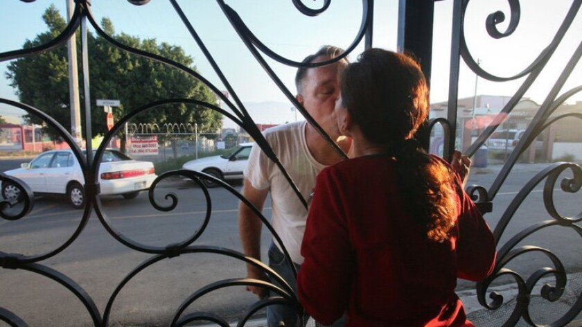 Michael Paulsen kisses his wife, Emma Sanchez, goodbye as he leaves Tijuana after a visit and returns to his job as an auto mechanic in Vista, Calif. Sanchez lives in Tijuana, while Paulsen and their three sons, Alex, Ryan and Brannon, live in Vista.