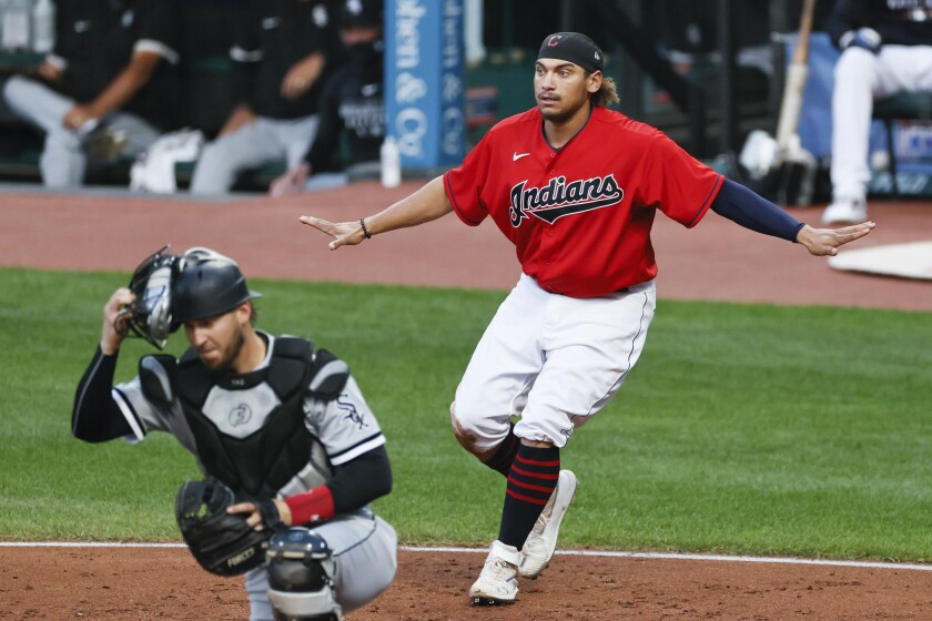 Cleveland Indians' Josh Naylor, right, signals safe after scoring past Chicago White Sox catcher Yasmani Grandal, left, on a single by Cesar Hernandez during the second inning of a baseball game, Monday, Sept. 21, 2020, in Cleveland. (AP Photo/Ron Schwane)