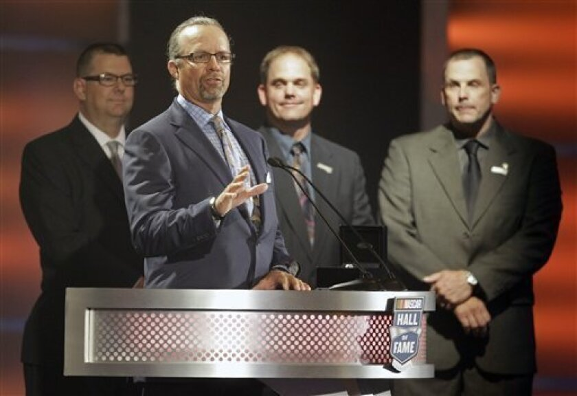Kyle Petty, second from left, speaks as Mark Petty, left, Tim Petty, second from right, and Ritchie Petty, right, look on as they help induct their grandfather Lee Petty into the NASCAR Hall of Fame during a ceremony in Charlotte, N.C., Monday, May 23, 2011. (AP Photo/Chuck Burton)
