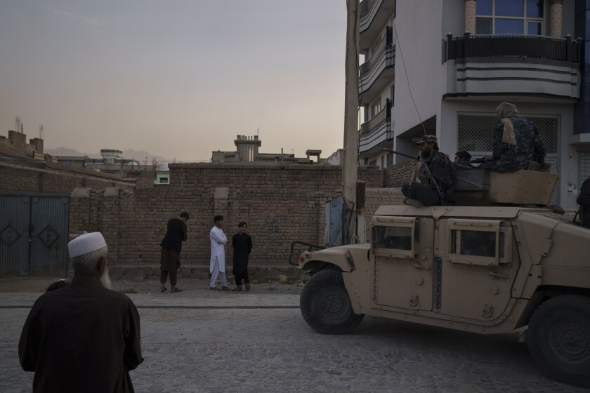Afghans watch as Taliban fighters ride atop a Humvee in Kabul.