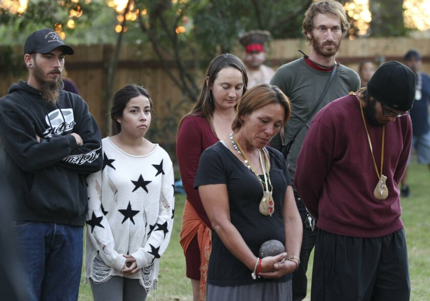People, many of them Native Americans, including Caroline Ward Holland, center, who walked to all 21 California Missions, stand with others during the Closing Ceremony for the Walk for the Ancestors at the Mission Basilica San Diego Alcalá in San Diego on Saturday.