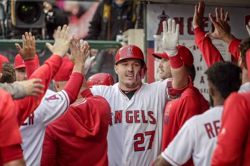 Angels' Mike Trout is greeted by teammates in the dugout during a game.