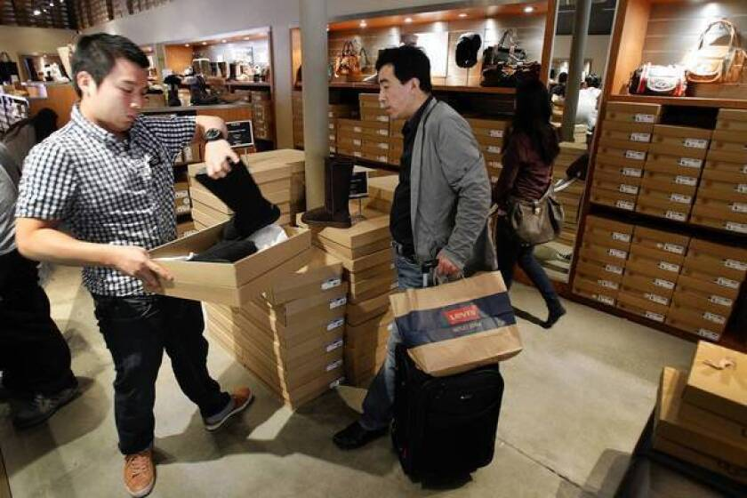 Chinese tourists spend an average of $2,932 per visit to California compared with $1,883 for other overseas visitors, according to the latest statistics by the U.S. Office of Travel and Tourism Industries. Above, Jeffrey Hsu, left, a Mandarin-speaking sales associate at the Ugg Australia store at the Desert Hills Premium Outlets in Cabazon, helps shopper Ding Sheng, a tourist from China, in March.