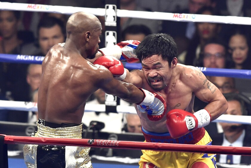 Floyd Mayweather Jr. and Manny Pacquaio trade punches during the fourth round of their May 2 fight in Las Vegas.