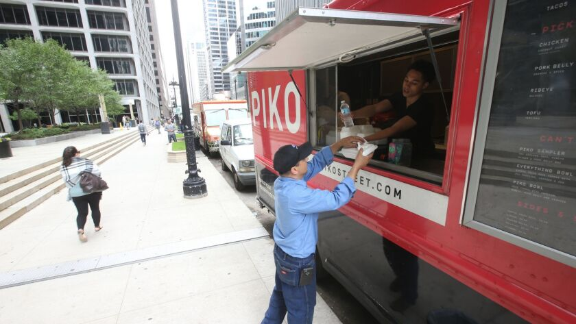 A customer takes his food from a food truck in the 100 block of South Wacker on June 1, 2018, as the trucks serve office workers and visitors. After a dispute among food truck operators at the spot Thursday, the police issued citations to trucks and many left the area.