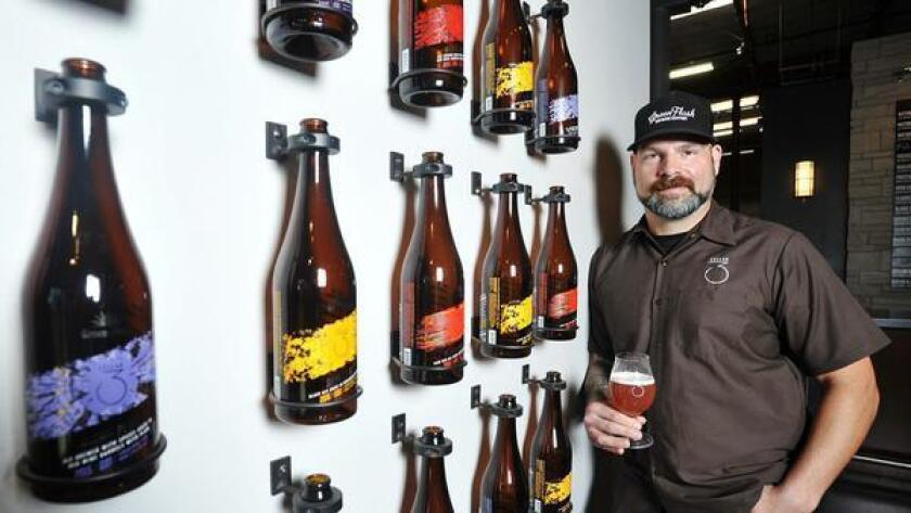 Jesse Smith, tasting room manager at Green Flash Brewing Company Cellar 3, stands in front of a bottle display of their barrel-aged brews.