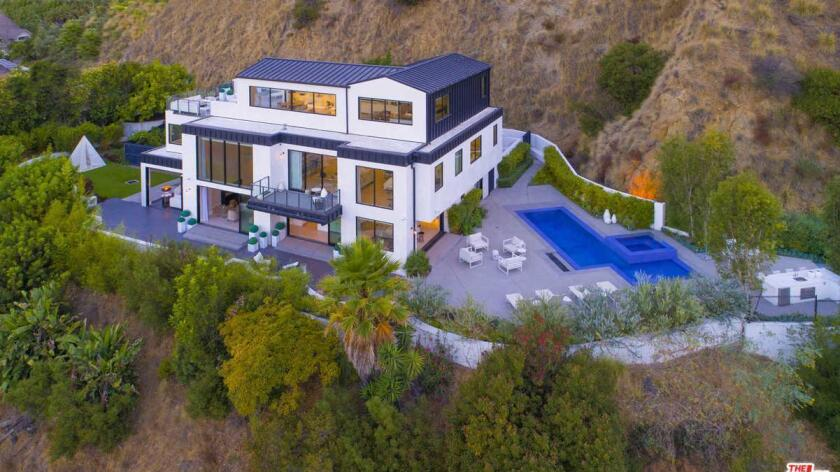 The three-story home sits on a gated acre just above Sunset Boulevard.