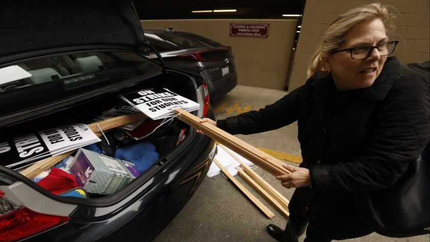 Teacher Pam Baron loads up her car with picket signs after a meeting with United Teachers Los Angeles about a possible strike in Los Angeles.