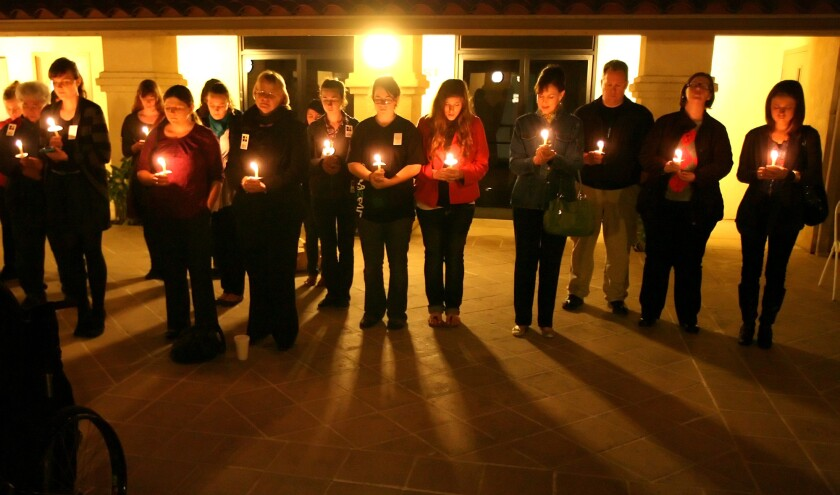 Students and activists participate in candlelight vigil for victims of human trafficking worldwide.