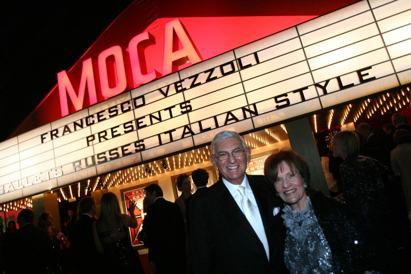 Eli Broad and wife Edythe stand in front of a lighted MOCA marquee.