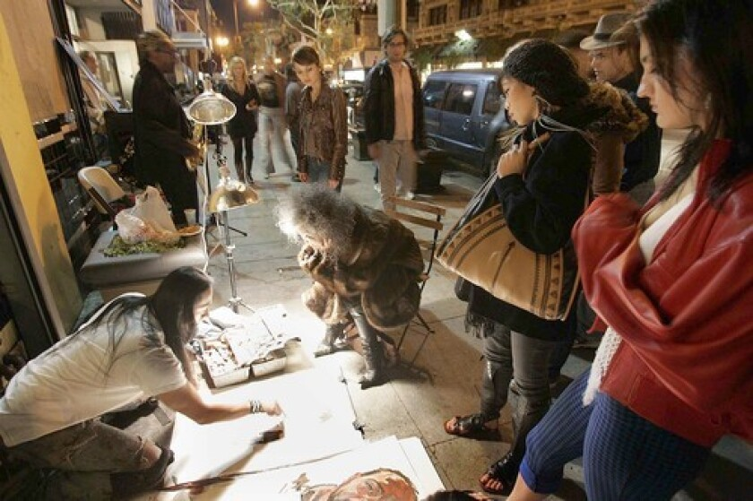 CARNIVAL ATMOSPHERE: A street artist painting a portrait draws a small crowd in downtown. The monthly art walk draws 2,000 to 3,000 visitors to more than 40 galleries.