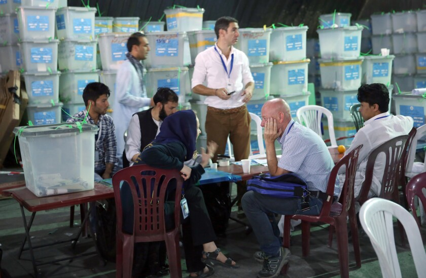 Afghan election commission workers sort ballots for an audit of the presidential runoff votes in front of international observers at an office in Kabul, Afghanistan.