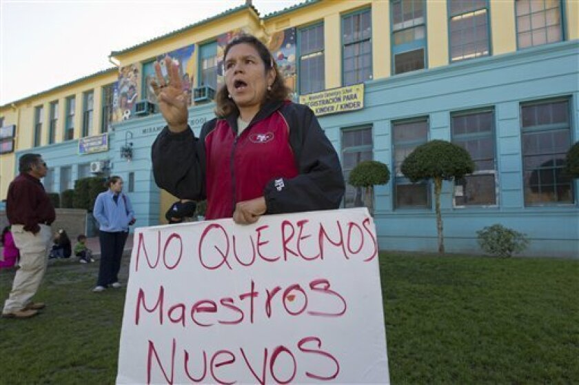 """Parent Maria Guadalupe Garcia holds a sign reading in Spanish: """" We don't want new teachers,"""" as some parents protest replacing the staff outside the Miramonte Elementary school in Los Angeles on Wednesday, Feb. 8, 2012. Allegations of teacher lewd behavior comes as school district administrators move to replace the entire staff at Miramonte Elementary School while the Los Angeles Unified School District investigates two teachers arrested last week. (AP Photo/Damian Dovarganes)"""