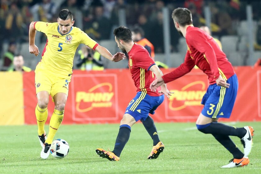 Spain's Mario Perez, center, and Gerard Pique challenge the ball with Romania's Ovidiu Stefan Hoban during a friendly soccer match between Romania and Spain in Cluj, Romania, Sunday, March 27, 2016. (AP Photo/Mircea Rosca)