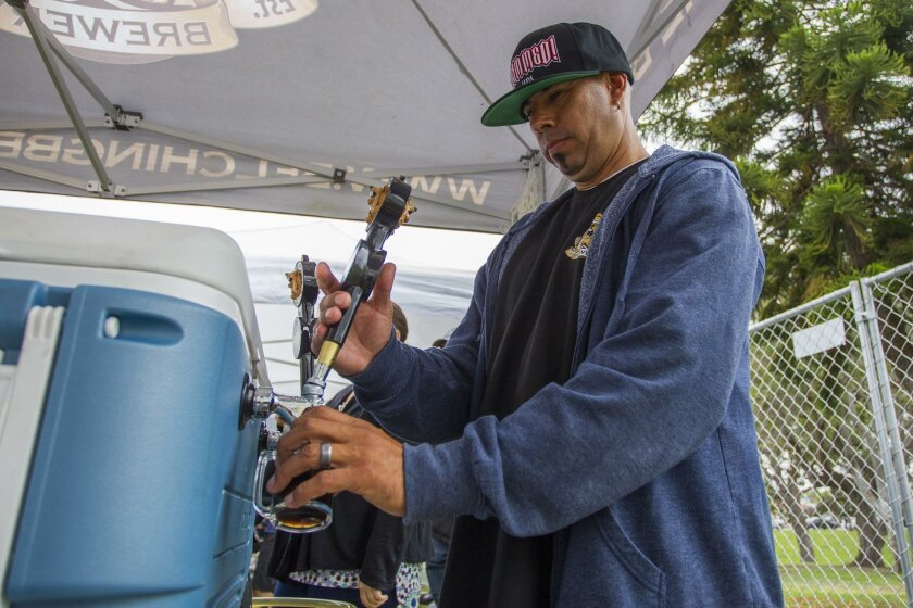 """Belching Beaver's Andrew """"Nacho"""" Morales pours one of the brewery's famous Peanut Butter Stouts for a festival guest."""
