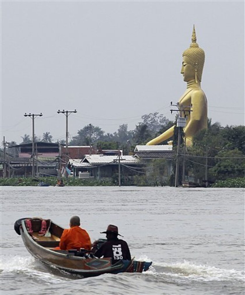 A passenger boat cruises on the Chaophraya river past a giant Buddha statue sitting among flooded houses in Pak Kred district, Nonthaburi province, Thailand Thursday, Oct. 13, 2011. The ongoing floods is the worst to hit the Southeast Asian nation in decades. About 8.2 million people in 60 of Thailand's 77 provinces have been affected by floods and mudslides, and 30 provinces are currently inundated. (AP Photo/Apichart Weerawong)