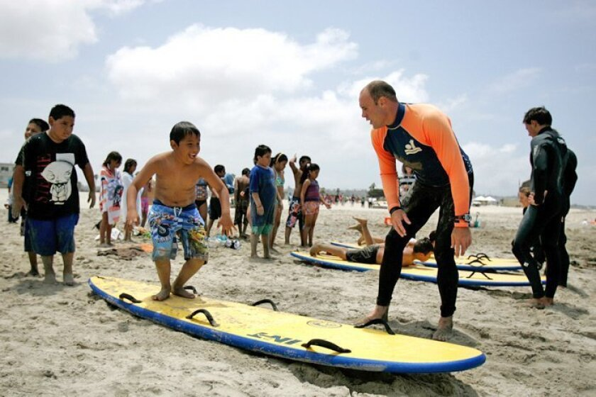San Diego lifeguard Christian Anderson (right) shows Eric Gutierrez, 9, a student at King-Chavez school in Logan Heights, the proper technique for standing up on a surfboard during an outing Friday at South Mission Beach.