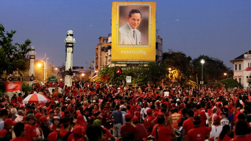Supporters of ousted Prime Minister Thaksin Shinawatra gather under a giant portrait of King Bhumibol Adulyadej in 2005.