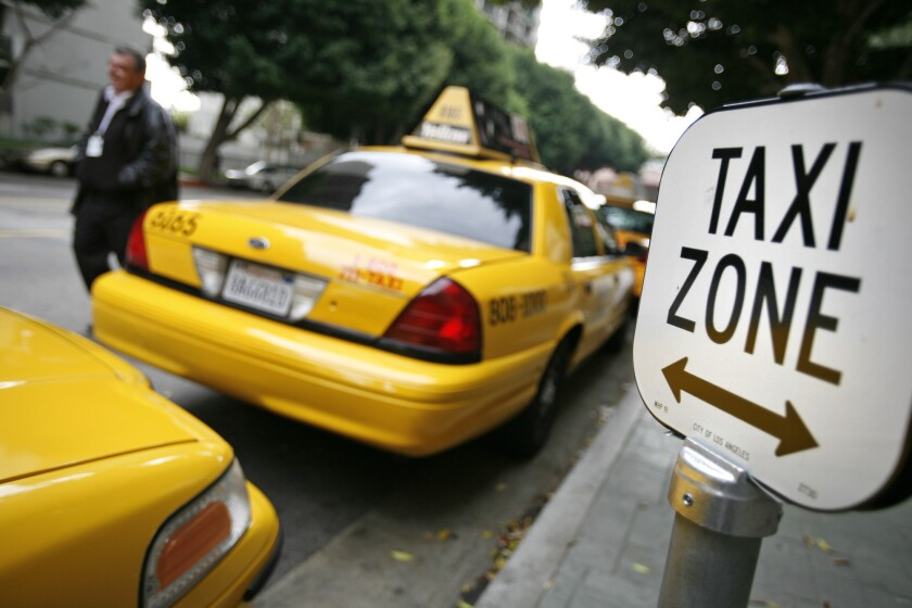 Taxis line up in front of the Omni Hotel in downtown Los Angeles, an area where drivers have lost much of their business to ride-hailing services.