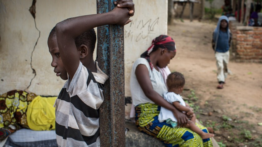 A woman and her children wait for medical attention in Luberizi, Congo.