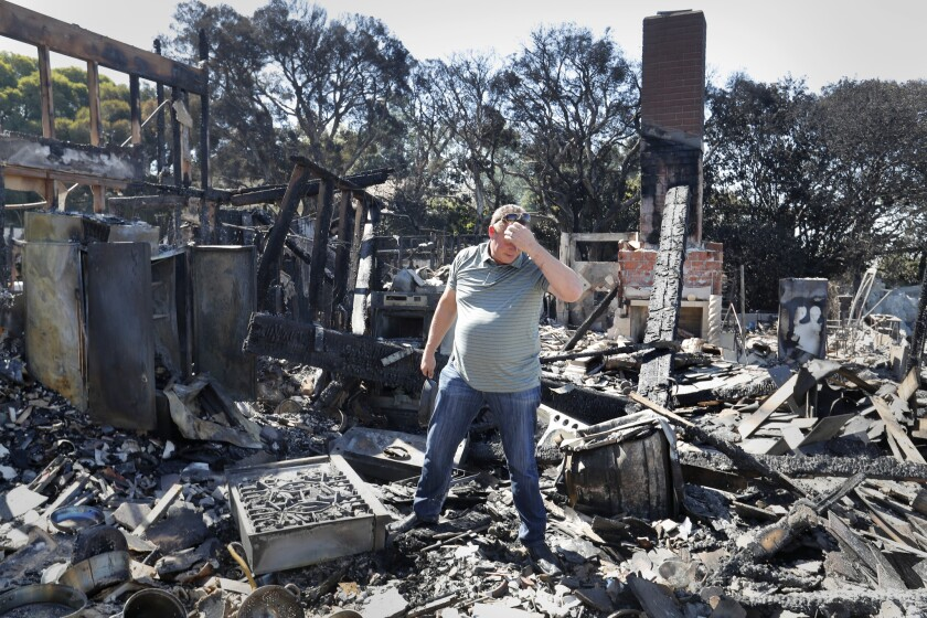 Holding a cast-iron skillet passed down to him from his grandmother, Danny Williamson looks through the remains of his home that was destroyed on Via El Estribo.