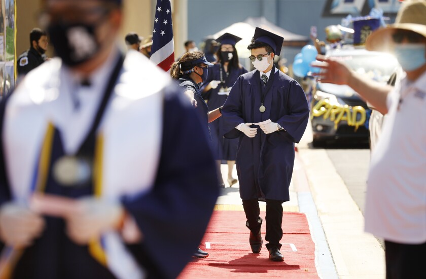 Graduates walk a red carpet to receive their diplomas in a drive-thru graduation ceremony