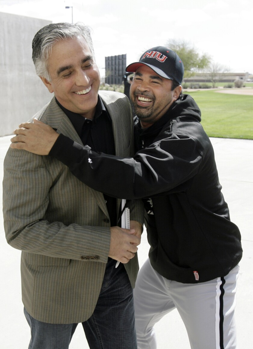 In this 2008 file photo, White Sox manager Ozzie Guillen, right, jokes with ESPN's Pedro Gomez after a news conference.