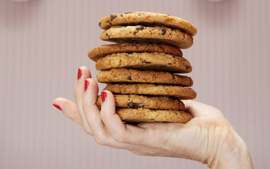 A manicured hand holds a stack of Vegan Gluten-Free Chocolate Chip Cookies