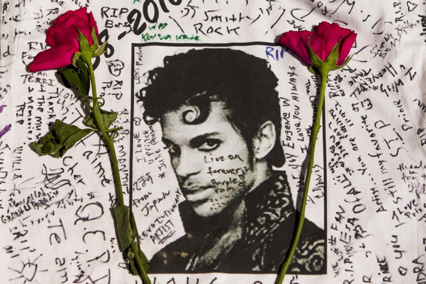 Flowers lay on a T-shirt signed by fans of singer Prince at a makeshift memorial outside the Apollo Theatre in New York on Friday.