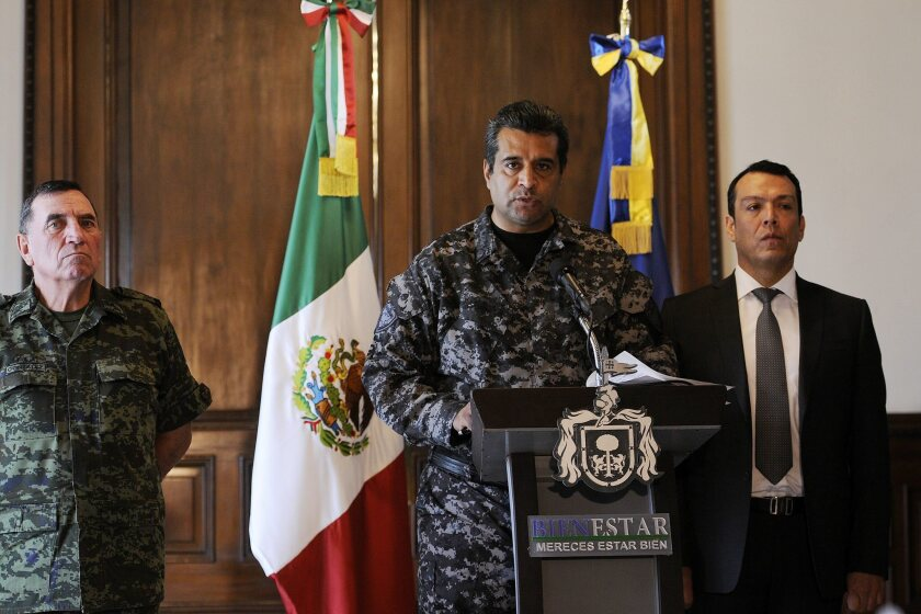 Alejandro Solorio, center, public security commissioner for Mexico's Jalisco state, speaks during a news conference in Guadalajara on April 7 about 15 police officers slain the day before.