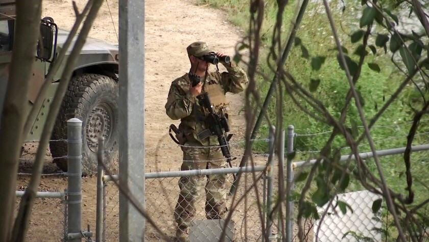 FILE - In this April 10, 2018, file frame from video, a National Guard troop watches over Rio Grande