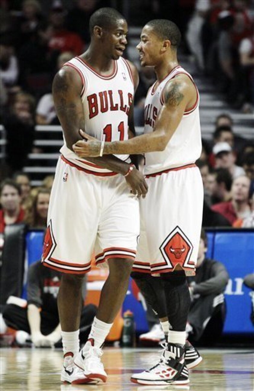 Chicago Bulls' Ronnie Brewer (11) celebrates with Derrick Rose (1) during the third quarter of an NBA basketball game against the Memphis Grizzlies in Chicago on Sunday, Jan. 1, 2012. (AP Photo/Nam Y. Huh)