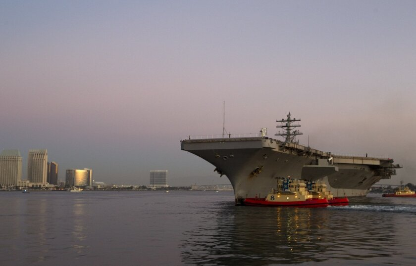 The Ronald Reagan departs its berth at North Island Naval Air Station for its trip to Washington state for a year-long overall.