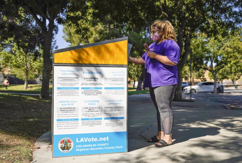 FILE - In this Oct. 14, 2020, file photo, a citizen drops her ballot at an official ballot drop box in Santa Clarita, Calif. California's leaders are considering making voting by mail a permanent option for all of its registered voters. This year, the state required county elections officials to mail a ballot to all registered voters ahead of the election. (AP Photo/Marcio Jose Sanchez, File)
