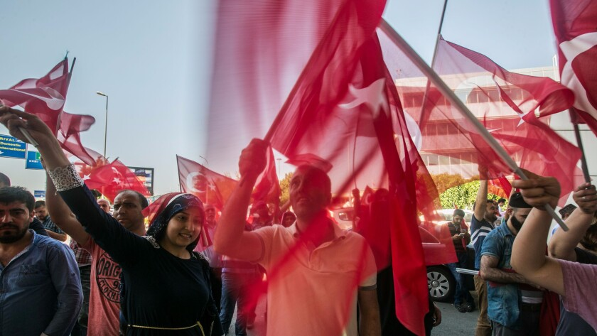 Turks wave flags at the Ataturk airport in Istanbul as they celebrate defeating a coup attempt.