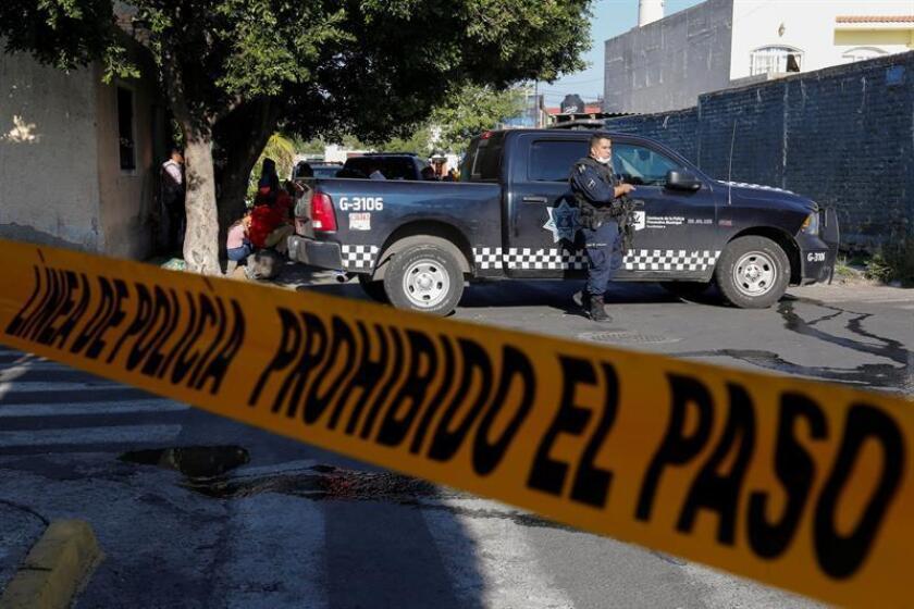 Policías municipales custodian una finca donde fueron hallados cuatro cadáveres en Guadalajara (México).