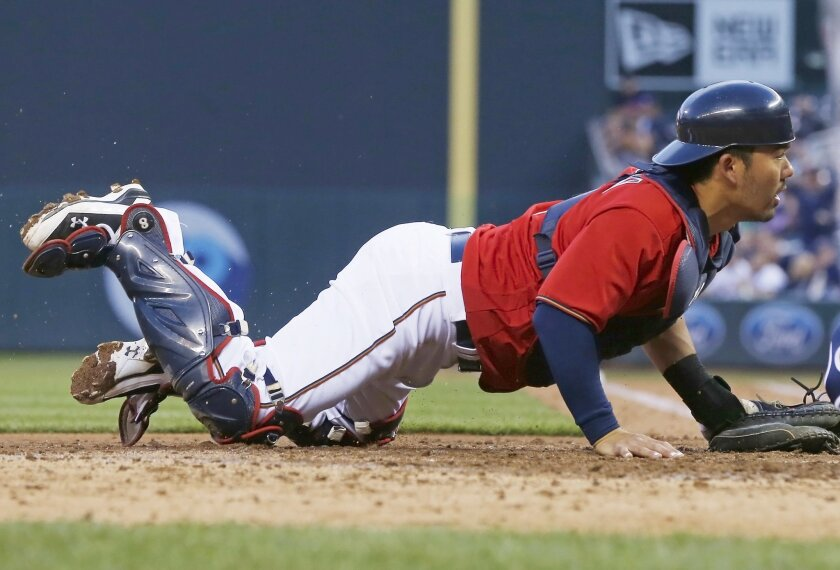 Minnesota Twins catcher Kurt Suzuki looks on as Tampa Bay Rays' Steven Souza Jr. beats Suzuki's tag to score on a sacrifice fly by Mike Mahtook, evening the score in the fifth inning of a baseball game Friday, June 3, 2016, in Minneapolis. (AP Photo/Jim Mone)