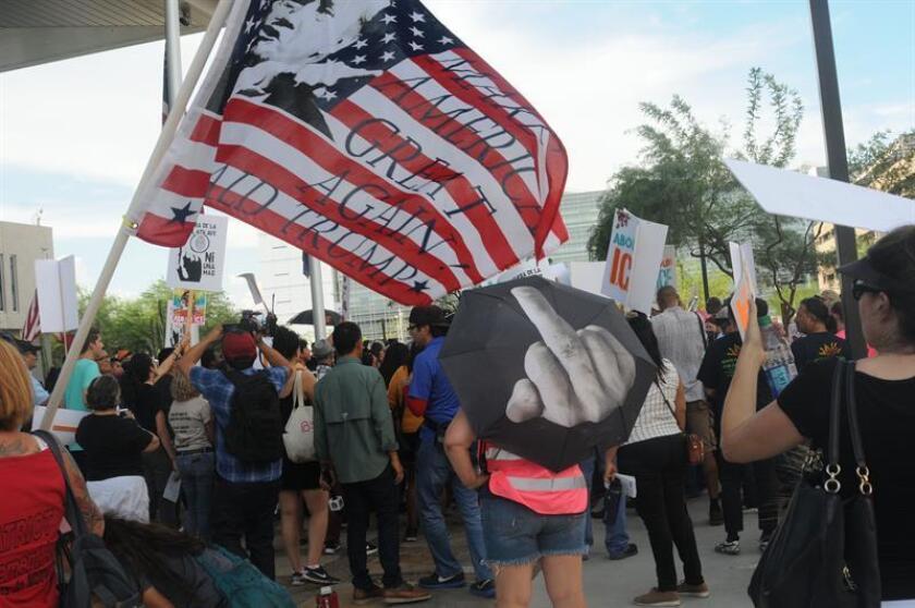 """Un simpatizante del presidente de EE.UU., Donald Trump, ondea una bandera nacional en la que se ve una imagen de Trumo y se puede leer el lema """"Make America Great Again"""", durante una concentración de decenas de miembros de la campaña """"Chinga La Migra"""" delante de la cárcel del Condado Maricopa el miércoles 22 de agosto de 2018, en Phoenix, Arizona (EE.UU.). EFE"""