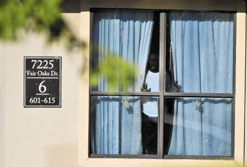 A child looks out from an apartment in Dallas where relatives of Thomas Eric Duncan, the Liberian who died of Ebola after arriving, are living.