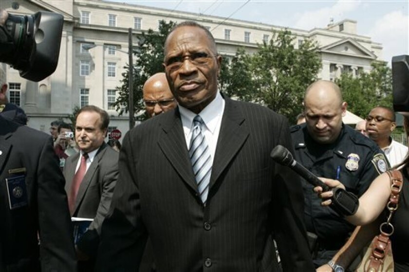 FILE - In this Tuesday, July 29, 2008 file photo, former Newark Mayor Sharpe James, center, leaves the U.S. District Court in Newark, N.J., after he was sentenced to more than two years in federal prison for his role in the cut-rate sales of city land to his former mistress. James, 77, was robbed Thursday, April 11, 2013, put in a chokehold and stripped of a gold chain and cross. He was not injured. (AP Photo/Mike Derer, File)