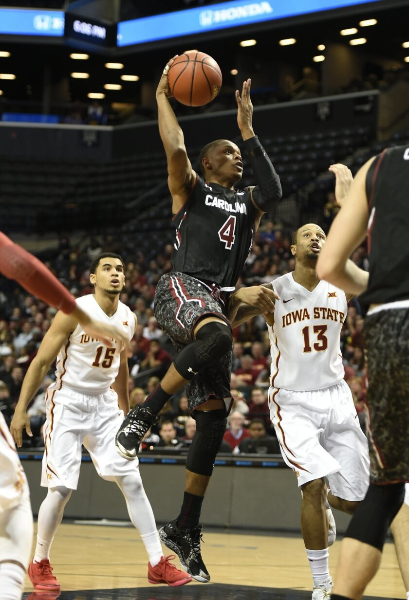 South Carolina guard Tyrone Johnson (4) shoots  between Iowa State guard Naz Long (15) and guard Bryce Dejean-Jones (13) during the first half of an NCAA college basketball game at Barclays Center on Saturday, Jan. 3, 2015 in New York. (AP Photo/Kathy Kmonicek)