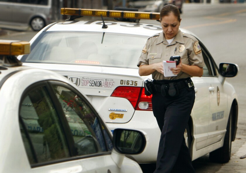A Los Angeles traffic officer walks back to her vehicle after a converstion with another officer on Echo Park Ave.