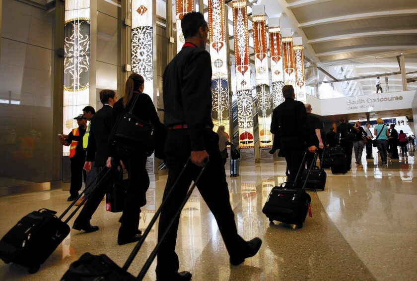Passengers roll carry-ons through Tom Bradley International Terminal at LAX. A study found that a lot of boarding time is wasted as passengers look for space in overhead compartments to stow their carry-on bags.