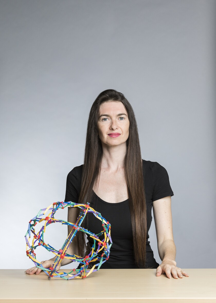 A woman in a black T-shirt stands behind a table with an expandable ball toy on it.