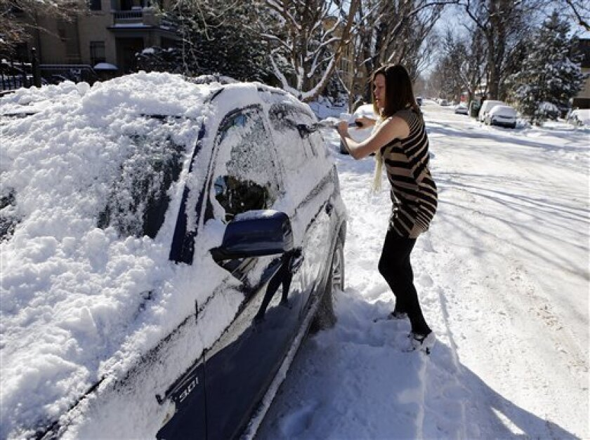Ayla Anderson, clears snow from her vehicle in Denver on Monday, Feb. 25, 2013. Anderson just moved to Denver from Florida. A winter storm passed through Colorado on Sunday dumping over a foot of snow in the Denver area. (AP Photo/Ed Andrieski)