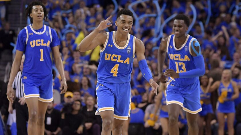 UCLA's Jaylen Hands, center, celebrates after hitting a three-point shot as Moses Brown, left, and Kris Wilkes follow during the Bruins' win over USC on Feb. 28.