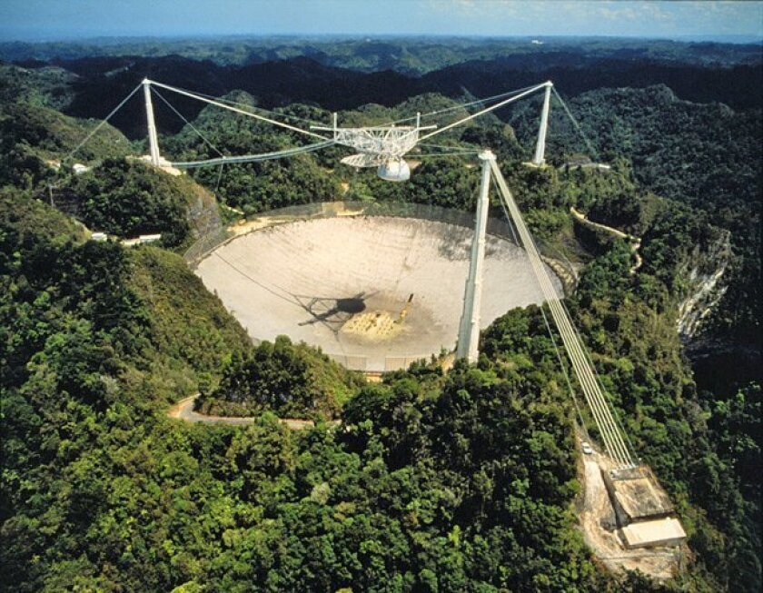If radio signals originated by extraterrestrial life are out there, SETI scientists aim to intercept them. The Arecibo radio telescope observatory (above), in Puerto Rico, is  one site among a growing number where the search, started 50 years ago, continues.