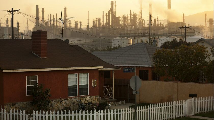 The Phillips 66 refinery looms over a neighborhood in the Wilmington neighborhood of Los Angeles. A fee increase adopted by Southern California officials will pay for a greater share of the costs of regulating toxic air pollution from refineries and other facilities.