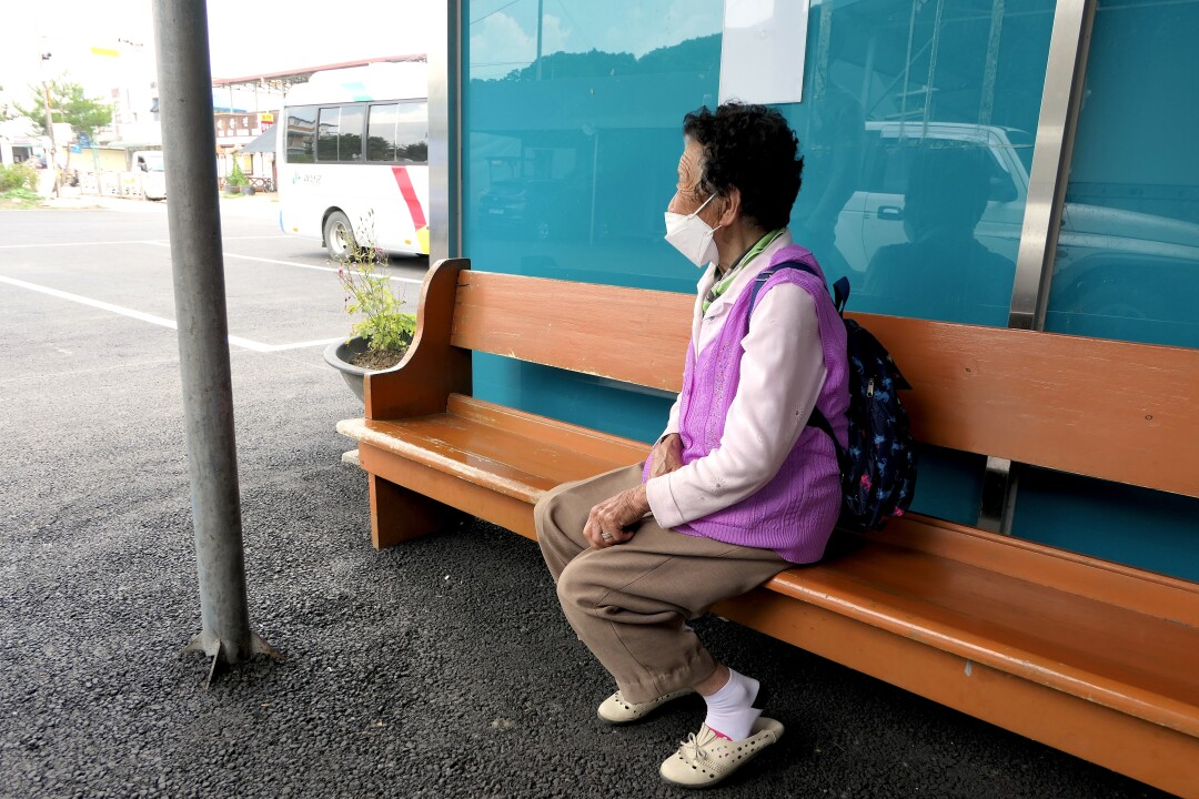 A woman wearing a knapsack sits on a bench