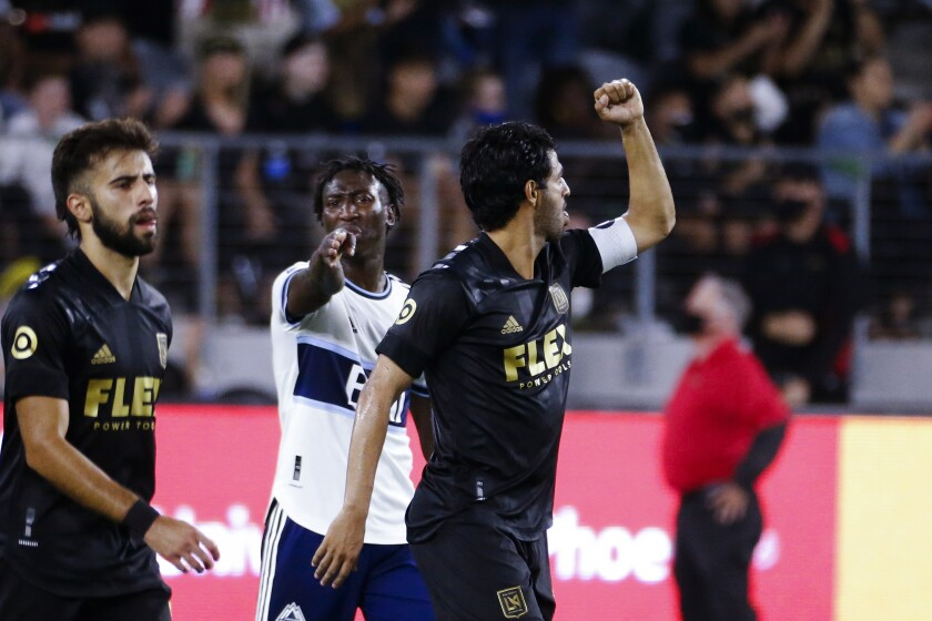 Los Angeles FC forward Carlos Vela, right, celebrates his goal during the first half of the team's MLS soccer match against the Vancouver Whitecaps in Los Angeles, Saturday, July 24, 2021. (AP Photo/Ringo H.W. Chiu)